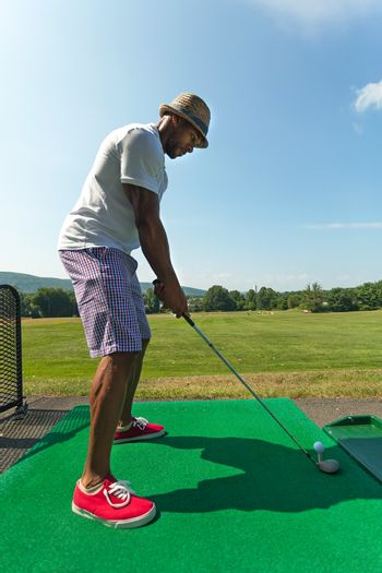 Athletic golfer teeing up at the driving range dressed in casual attire.