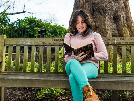 Pretty Woman Reading Book on Park Bench