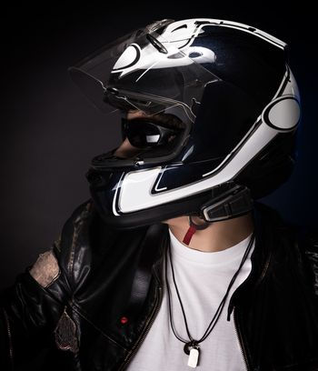 Portrait of stylish biker over dark background, nice teen boy wearing helmet and other bikers outfit, enjoying extreme sport, active lifestyle