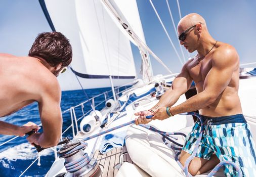 Two handsome sailors on sailboat