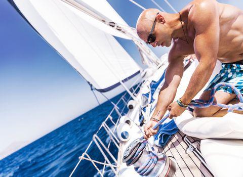 Handsome sailor on sailboat