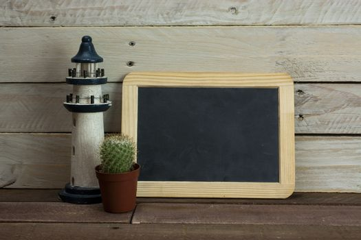 Lighthouse and blackboard against a wood background