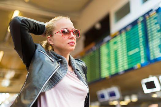 Female traveller checking flight departures board.