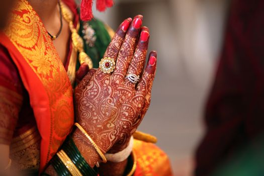 Folder hands of a traditional Indian bride in wedding attire, praying during her wedding.