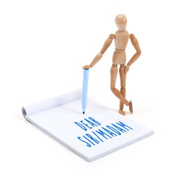 Wooden mannequin writing in scrapbook - Dear sir madam