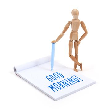 Wooden mannequin writing in scrapbook - Good morning