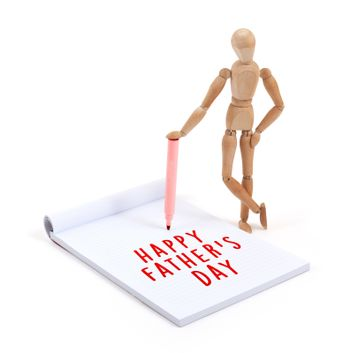 Wooden mannequin writing in scrapbook - Happy fathers day