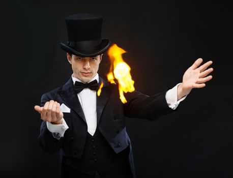 magician in top hat showing trick with fire