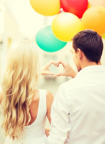 summer holidays, celebration and dating concept - couple with colorful balloons making heart shape in the city