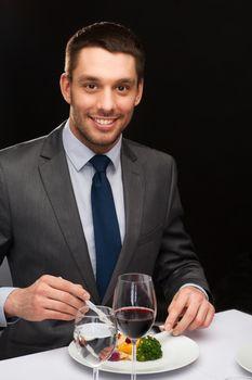 smiling man eating main course