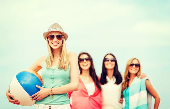 girl with ball and friends on the beach