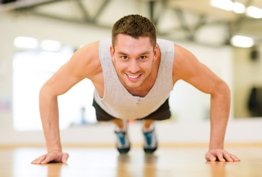 smiling man doing push-ups in the gym