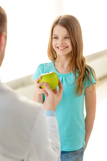 healthcare, child and medicine concept - male doctor giving an apple to smiling little girl