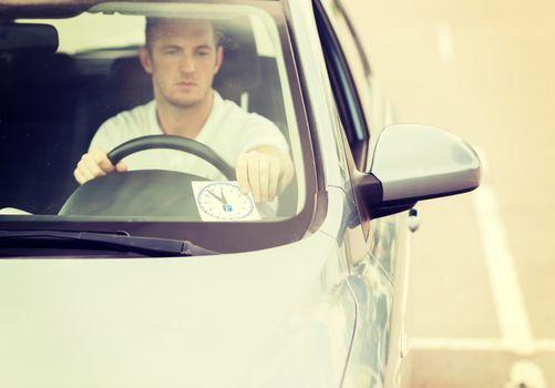 man placing parking clock on car dashboard