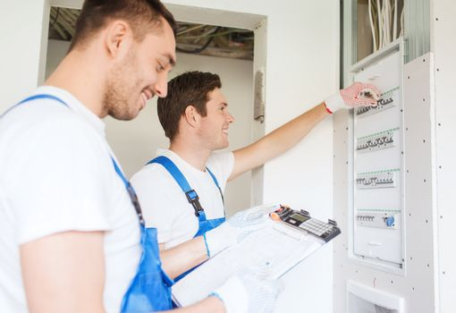 builders with clipboard and electrical panel