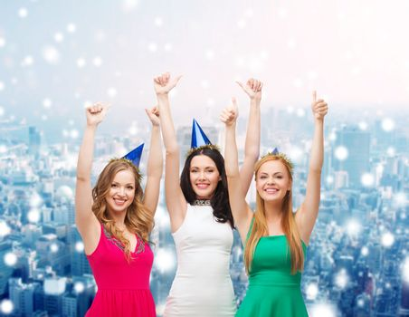 holidays, christmas, people, gesture and celebration concept - smiling women in party caps showing thumbs up over snowy city background