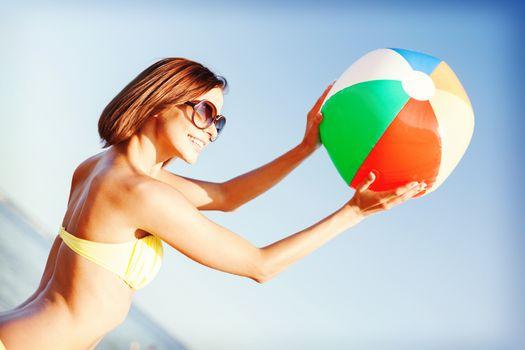 girl in bikini playing ball on the beach