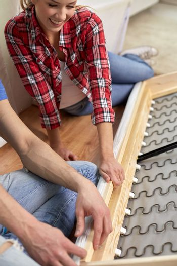 close up of couple assembling furniture at home