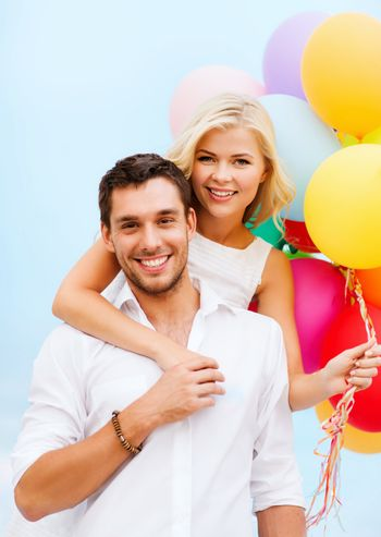 summer holidays, celebration and dating concept - couple with colorful balloons at seaside