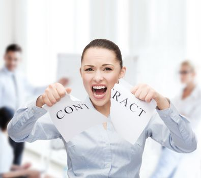 serious businesswoman tearing contract
