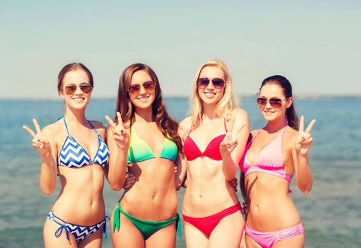 summer vacation, holidays, gesture, travel and people concept- group of smiling young women showing peace or victory sign on beach