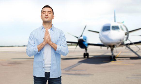 man praying over airplane on runway background