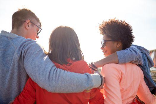 happy teenage friends in shades hugging on street