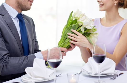 restaurant, people, celebration and holiday concept - smiling young couple with glasses of red wine looking at each other at restaurant