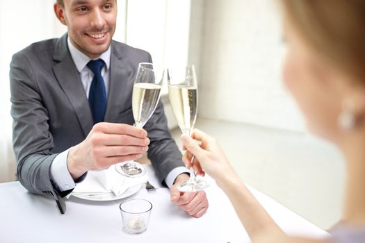 restaurant, people, celebration and holiday concept - close up of happy couple with glasses of champagne looking at each other at restaurant