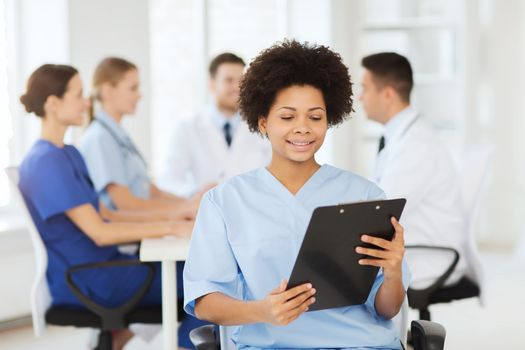 clinic, profession, people and medicine concept - happy female doctor or nurse with clipboard over group of medics meeting at hospital