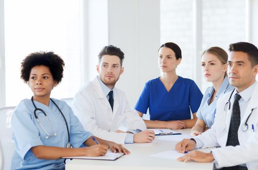 hospital, profession, people and medicine concept - group of happy doctors meeting on conference at hospital