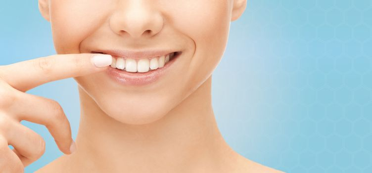 dental health, beauty, hygiene and people concept - close up of smiling woman face pointing to teeth over blue background