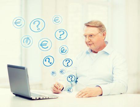 old man in eyeglasses filling a form at home