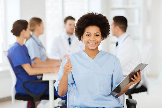 clinic, profession, people and medicine concept - happy female doctor or nurse with clipboard over group of medics meeting at hospital showing thumbs up gesture
