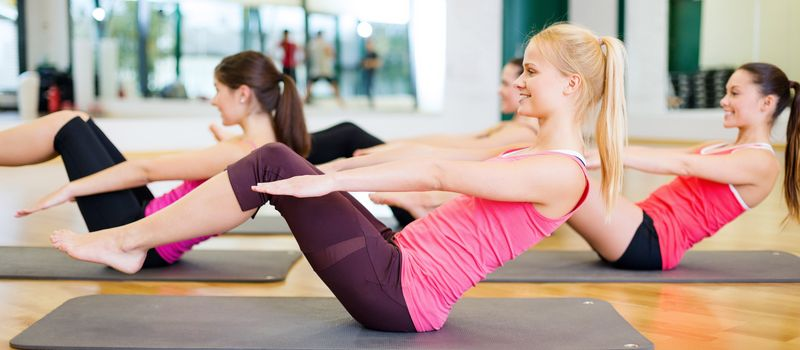 fitness, sport, training, gym and lifestyle concept - group of smiling women exercising on mats in the gym
