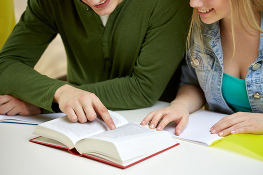 close up of students reading book or textbook