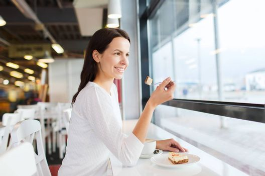 leisure, drinks, people and lifestyle concept - smiling young woman eating cake and drinking coffee at cafe