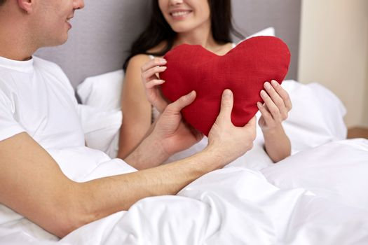 hotel, travel, relationships, holidays and happiness concept - close up of smiling couple in bed with red heart-shaped pillow at hotel or home