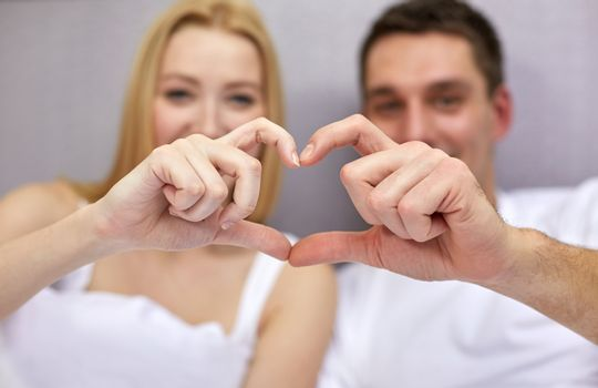 love, people and happiness concept - close up of smiling couple in bed making heart shape gesture