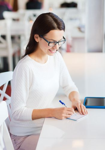 leisure, business, people, technology and lifestyle concept - smiling young woman in eyeglasses with tablet pc computer and notebook taking notes at cafe