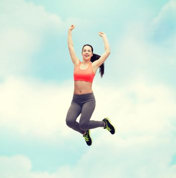 fitness and diet concept - beautiful sporty teenage girl jumping in sportswear