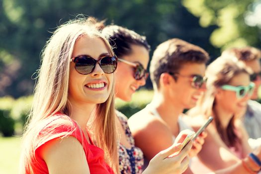 friendship, leisure, summer, technology and people concept - group of smiling friends with smartphones sitting in park