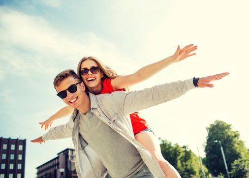 holidays, vacation, love and friendship concept - smiling couple having fun in city