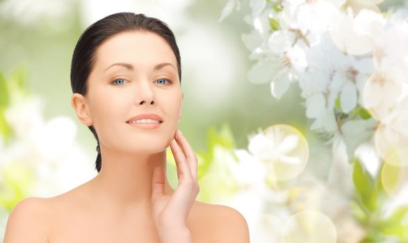 beauty, people and health concept - beautiful young woman touching her face over green blooming garden background