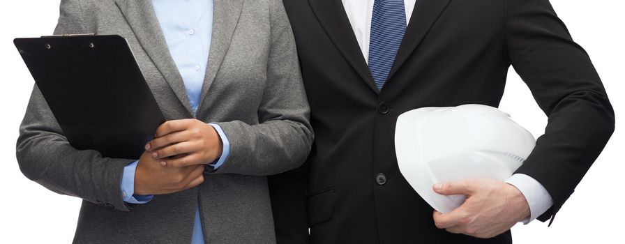 business, architecture and development concept - businesswoman and businessman with clipboard and white helmet