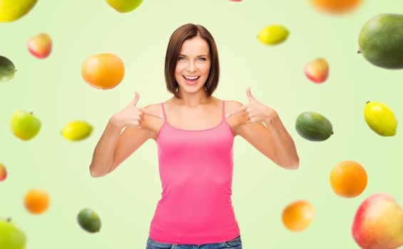 people, advertisement, diet, food and healthy eating concept - smiling woman in blank pink tank top pointing fingers to herself over fruits on green background