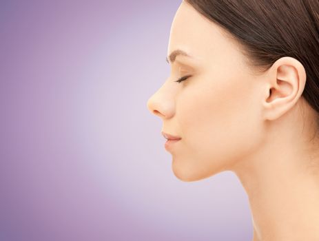 health, people, plastic surgery and beauty concept - beautiful young woman face over violet background