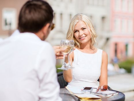 summer holidays and dating concept - woman drinking wine with man in cafe in the city