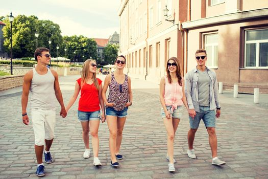 friendship, travel, tourism, summer vacation and people concept - group of smiling teenagers walking in the city