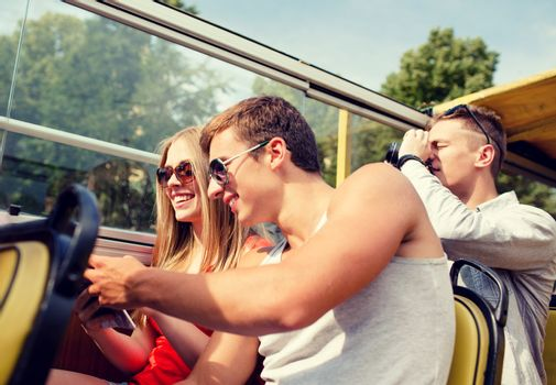 friendship, travel, vacation, summer and people concept - smiling couple looking to city guide book traveling by tour bus